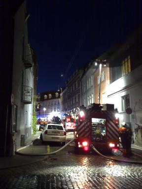 Firetrucks, policecar, and the street with the burned out building